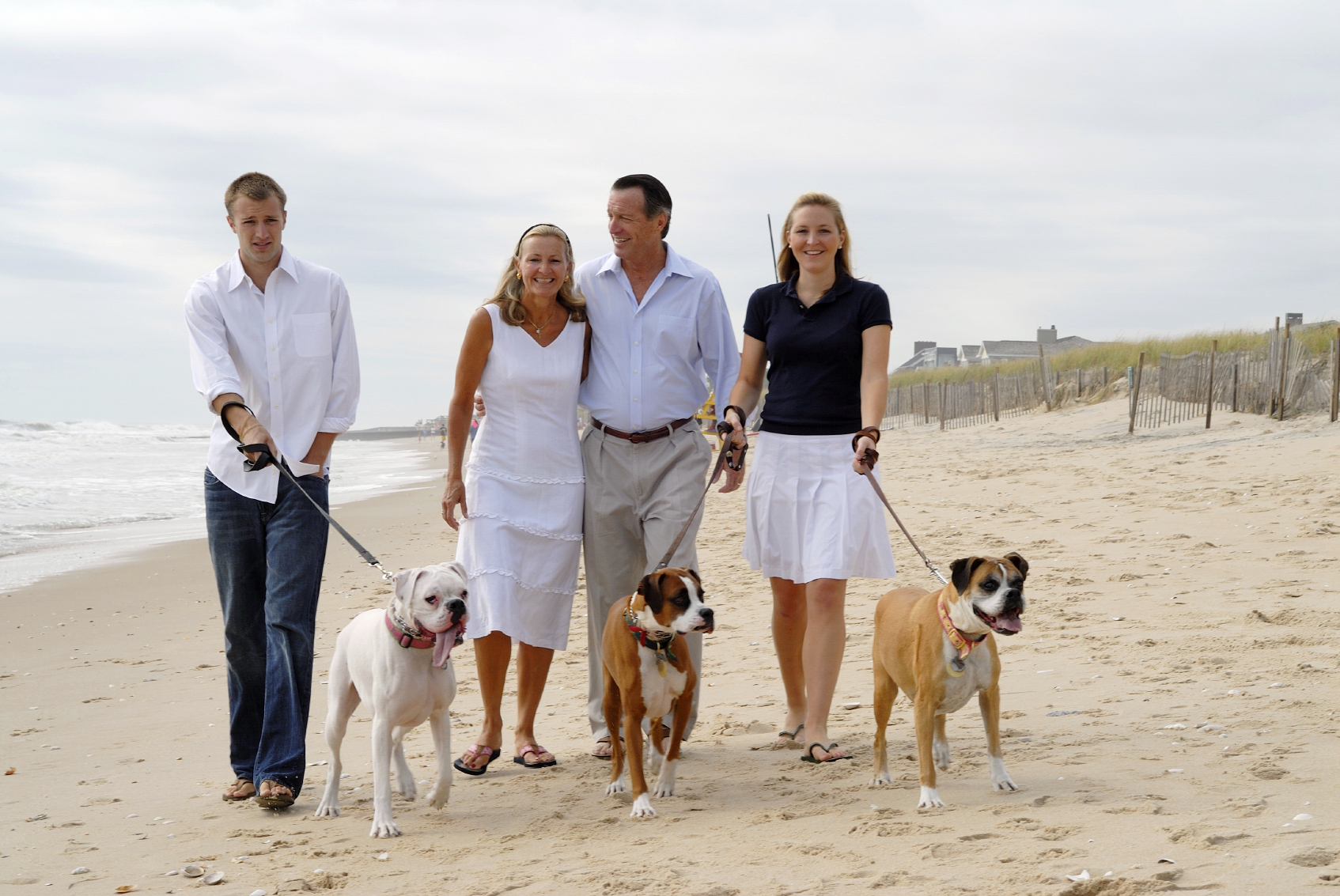 two couples walking their dogs on the beach